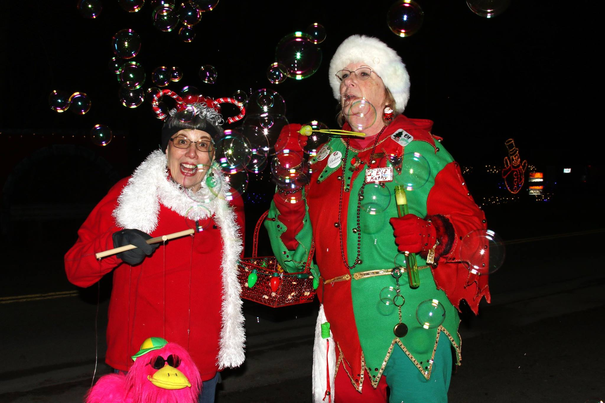 two female volunteer elves at the north pole blowing bubbles and smiling