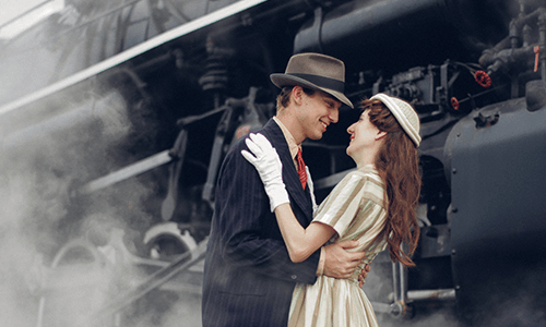 couple dressed in 1940s attire embracing each other in front of steam engine.