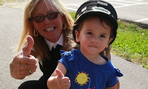 trainwoman and toddler wearing trainwoman's hat giving thumbs up