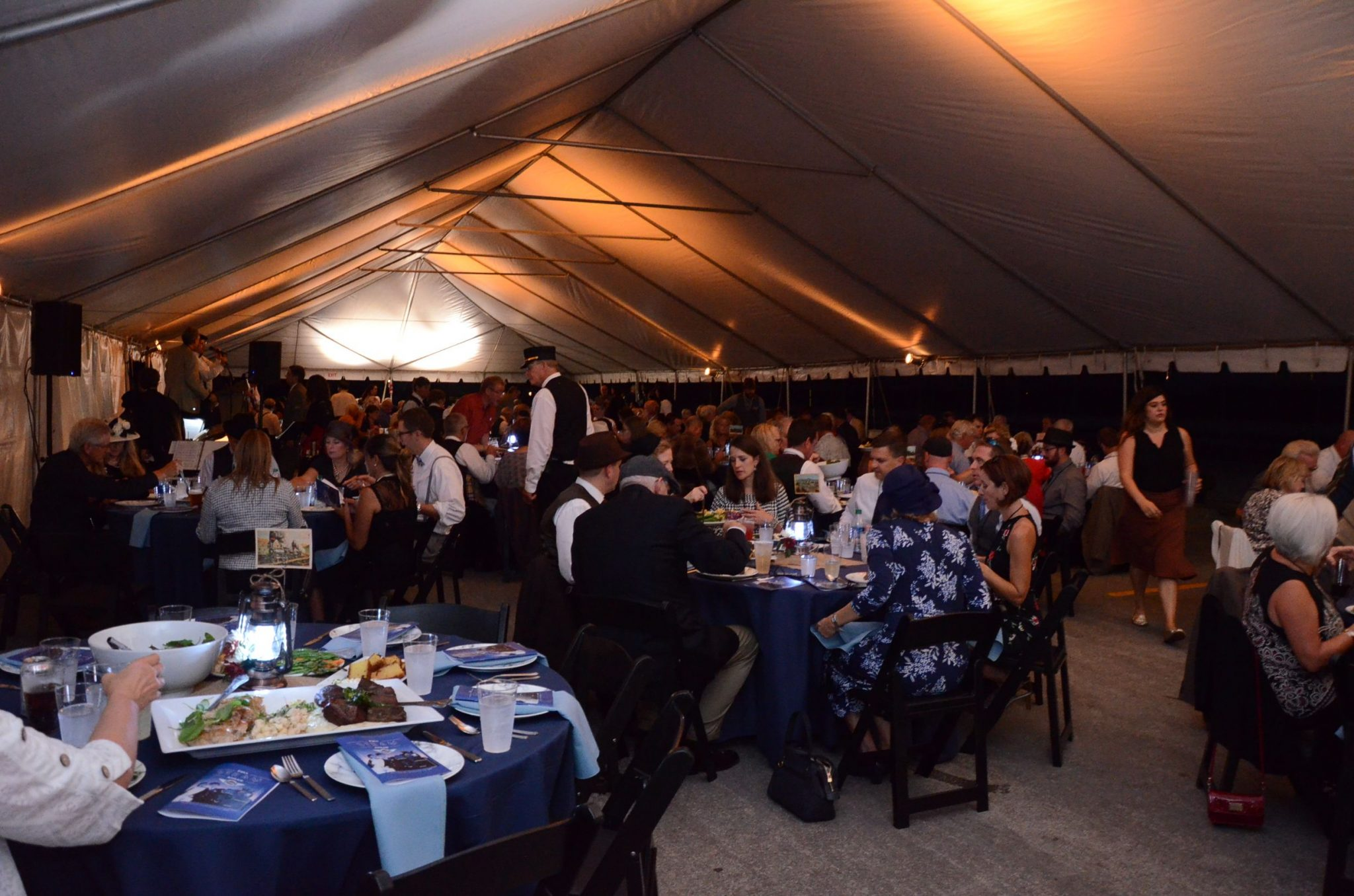 guests dine at tables under a large tent