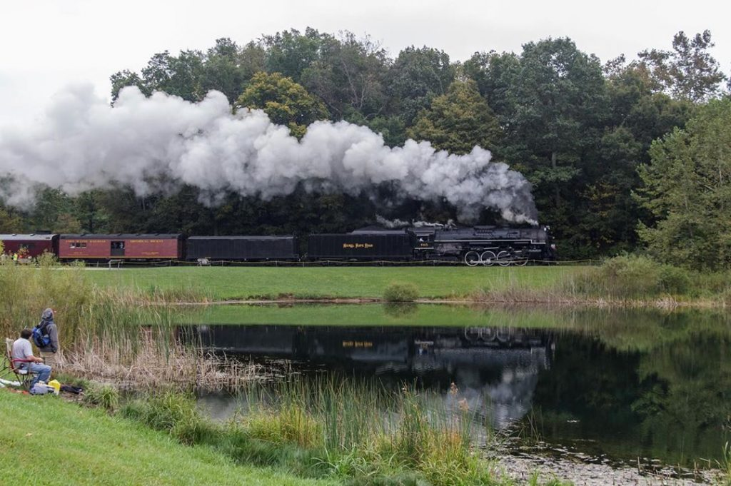 steam engine number 765 chugging past indigo lake with reflection on water